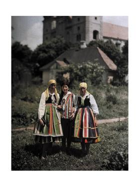 Three Girls Stand Together in Front of a Church by Hans Hildenbrand