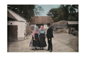 Two Women and a Man Visit in a Village Wearing Folk Costume by Hans Hildenbrand