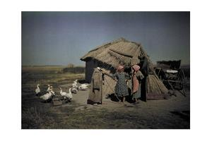Women Stand in Front of a Primitive Straw Covered Hut by Hans Hildenbrand