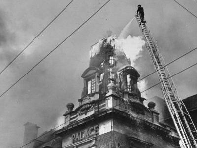 Fireman on Ladder Using a Hose to Extinguish Blazing Building Set Afire by Hans Wild