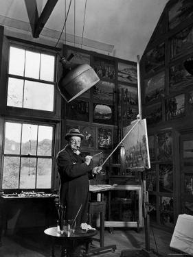 Former PM Winston Churchill Smoking a Cigar in His Studio Dressed in His Blue RAF Siren Jump Suit by Hans Wild