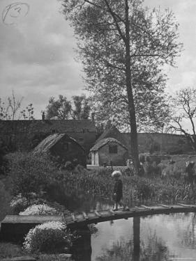 Little Boy Crossing the Bridge over the Stream at Winson Mill Farm, A War Nursery by Hans Wild
