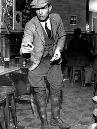 Man Playing Quoits, Like Horse Shoes, in an English Pub by Hans Wild