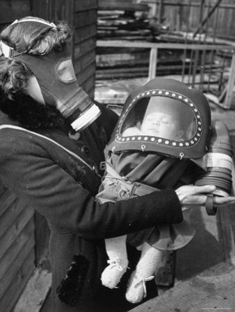 Mother and Baby Wearing Gas Masks During Gas Preparations Test During WWII by Hans Wild