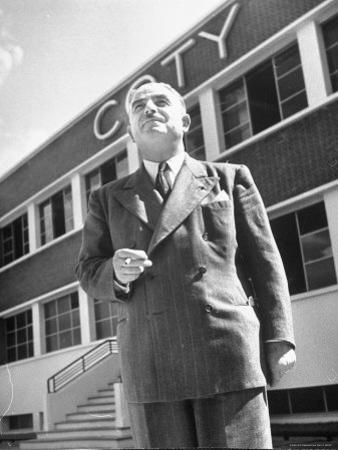 President and Director of Coty Perfumes Andre Lavault in Front of Building Holding Cigarette