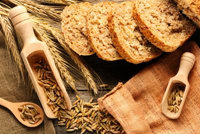 Rye Spikelets and Bread on Wooden Background by haveseen