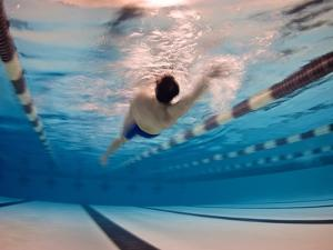 A Man Swimming the Back Stroke in an Indoor Swimming Pool by Heather Perry