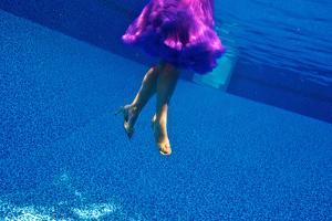 A Model Floats in a Pool, Wearing a Skirt and Heels by Heather Perry