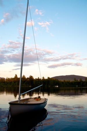 A Small Sailboat Anchored in a Pristine Lake by Heather Perry