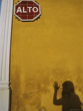 A Womans Shadow Cast on a Wall with a Stop Sign by Heather Perry