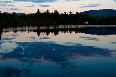 Clouds Reflect in a Scenic Pristine Lake, Lined with Evergreen Trees, at Sunrise by Heather Perry
