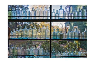 Vintage Blue Glass Bottles Against a Window