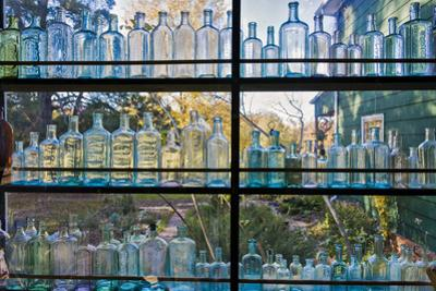 Vintage Blue Glass Bottles Against a Window by Henri Silberman