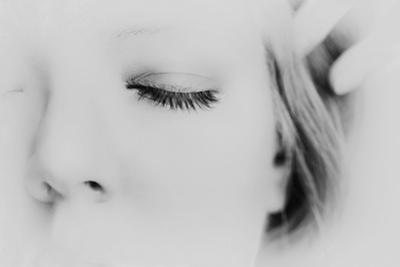 Close-Up of One Side of Young Woman's Face with Focus on the Eyelashes of Her Closed Eye by Henriette Lund Mackey