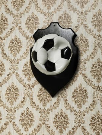 Punctured Football Hanging as a Trophy on a Wall by Henrik Sorensen