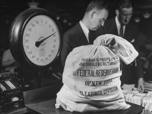 Bag of Checks Being Weighed on Scale at Bank by Herbert Gehr