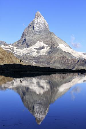 https://imgc.allpostersimages.com/img/posters/hiker-admiring-the-matterhorn-reflected-in-lake-stellisee-swiss-alps_u-L-Q12SCHO0.jpg?artPerspective=n