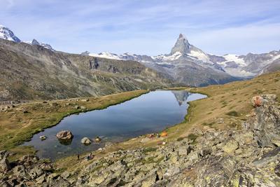 https://imgc.allpostersimages.com/img/posters/hikers-admire-the-matterhorn-reflected-in-lake-stellisee-swiss-alps_u-L-Q12SB9I0.jpg?p=0