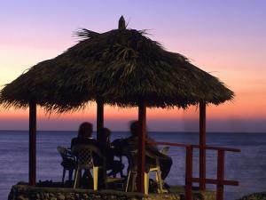 Cliffside Table at Pickled Parrot at Sunset, Negril, Jamaica by Holger Leue
