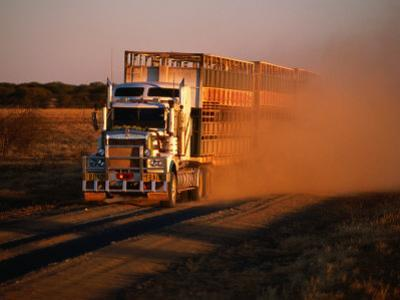 Road Train Driving along Dusty Road, Kynuna, Australia by Holger Leue