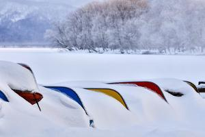 Japan, Hokkaido, Lake Kussharo. Colorful Canoes in the snow by Hollice Looney