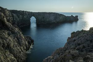 Spain, Menorca. Sunset at Pont d'En Gil (natural arch). by Hollice Looney