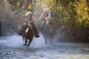 USA, Wyoming, Shell, The Hideout Ranch, Cowboy and Cowgirl on Horseback Running through the River by Hollice Looney