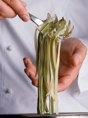 Chef Holding Pasta Over Pot by Howard Sokol