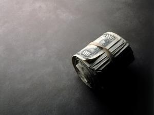 Roll of Money Held Together with Rubber Band by Howard Sokol