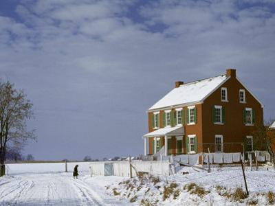 Huddled Figure Walks Up a Snow-Covered Road to an Amish Farmhouse