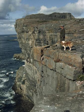 Irishman with His Dog Admire the View of the Ocean from a Cliff