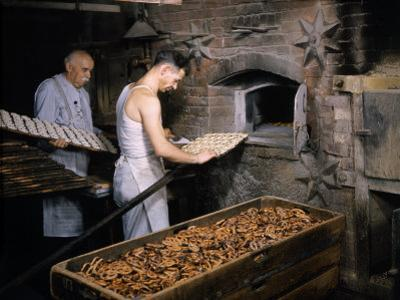 Men Load Trays of Pretzels into a Bakery's Old-Fashioned Oven