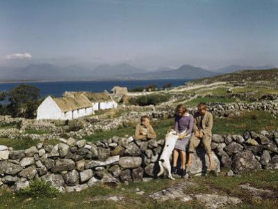 Teenagers Relax on a Stonewall Near their Home in Connemara