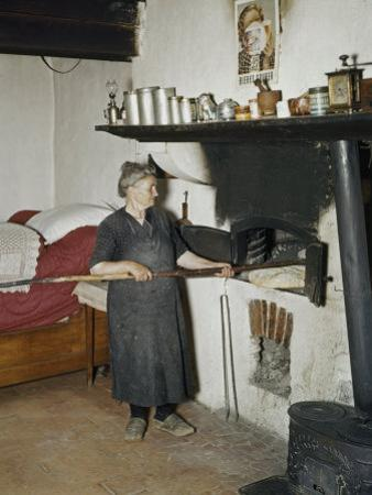 Woman Bakes Bread in Her One Room House