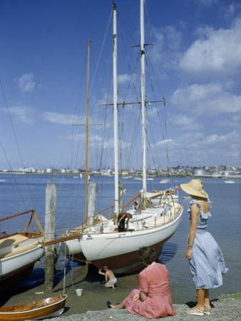 Women Watch Sailors Painting Ocean-Going Schooner's Hull at Low Tide
