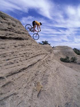 Active Male Rides Slickrock Ridge, Utah, USA by Howie Garber