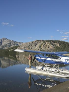 Fisherman and Floatplane, Takahula Lake, Alaska, USA by Hugh Rose