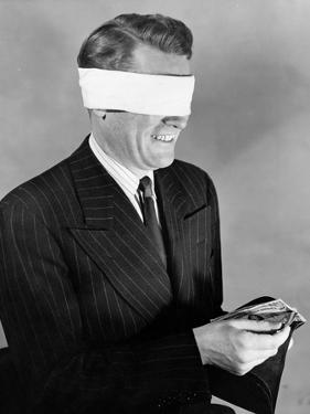 Man Wearing Blindfold Holding Money (B&W) by Hulton Archive