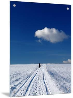 Man Walking in the Snow under Blue Skies by I.W.