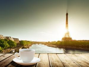Coffee on Table and Eiffel Tower in Paris by Iakov Kalinin