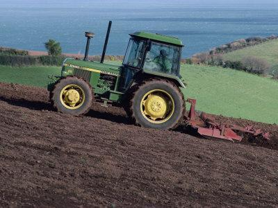 John Deere Tractor with a Rotivator on a Sloping Field in Spring, at Holcombe, Devon, England, UK
