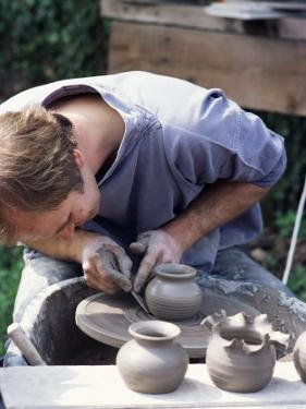 Potter at Work on Wheel at Rustic Fayre, Devon, England, United Kingdom by Ian Griffiths