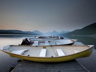 Glacier National Park- Boats Rest on a Dock in Front of Lake Mcdonald. by Ian Shive