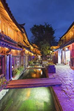 Bars and restaurants along canal at dusk, Lijiang, UNESCO World Heritage Site, Yunnan, China, Asia by Ian Trower
