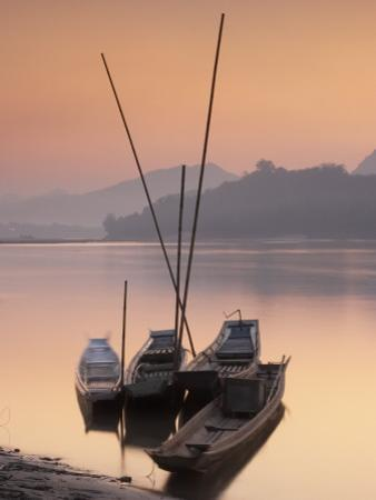 Boats on Mekong River at Sunset, Luang Prabang, Laos by Ian Trower