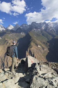 Man hiking in Tiger Leaping Gorge, UNESCO World Heritage Site, with Jade Dragon Snow Mountain (Yulo by Ian Trower