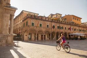 Woman Cycling Through Piazza Del Popolo, Ascoli Piceno, Le Marche, Italy by Ian Trower