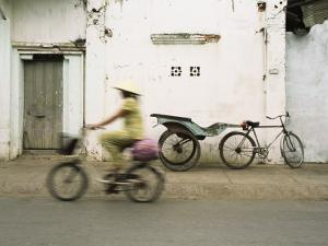 Woman Riding Bicycle Along Street, Ben Tre, Vietnam by Ian Trower