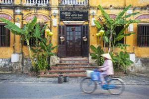 Woman Riding Bicycle Past Restaurant, Hoi an (Unesco World Heritage Site), Quang Ham, Vietnam by Ian Trower