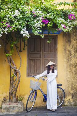 Woman Wearing Ao Dai Dress with Bicycle, Hoi An, Quang Ham, Vietnam by Ian Trower